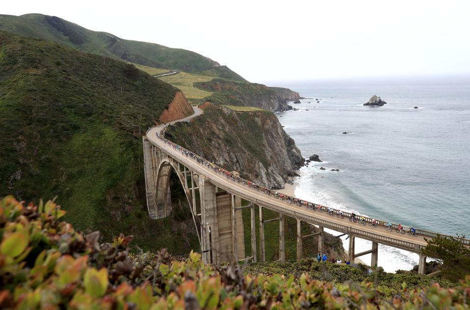 BIG SUR, CALIFORNIA - Peloton rides over the Bixby Creek Bridge. Big Sur, California.