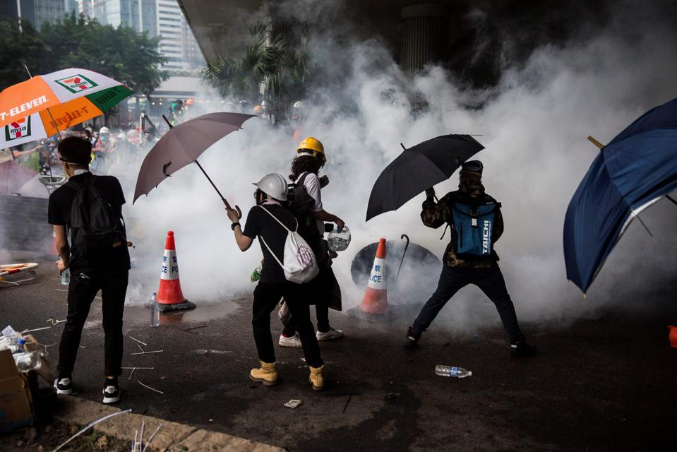 Protesters shielding themselves from tear gas, seen here as white clouds.