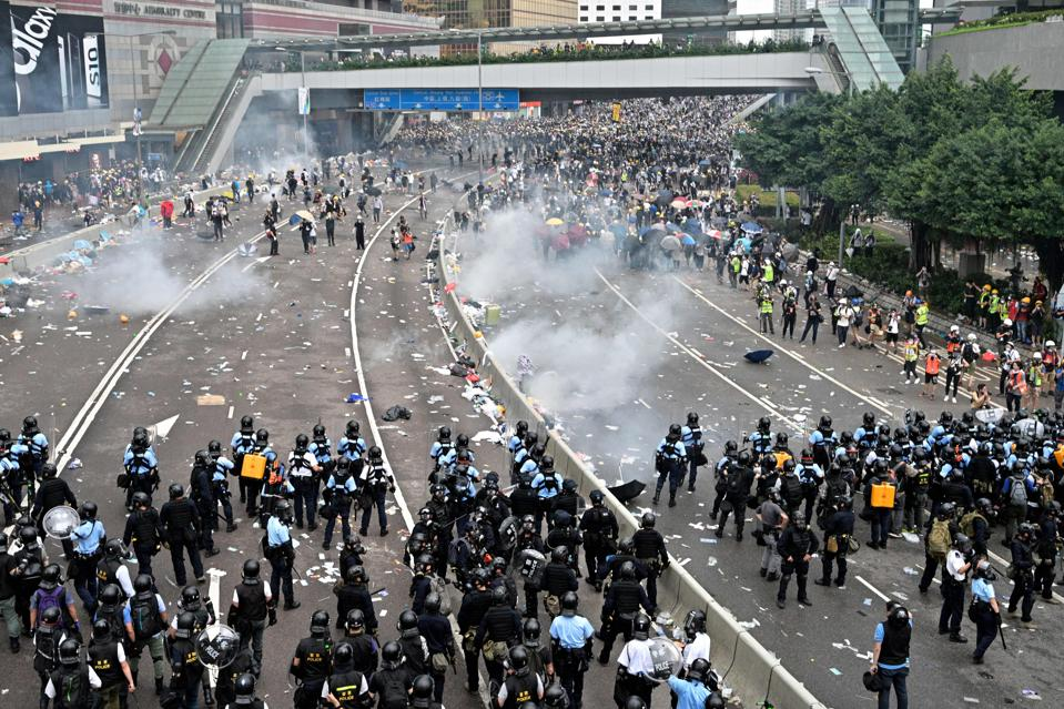 Protesters disperse after police fire tear gas at them.