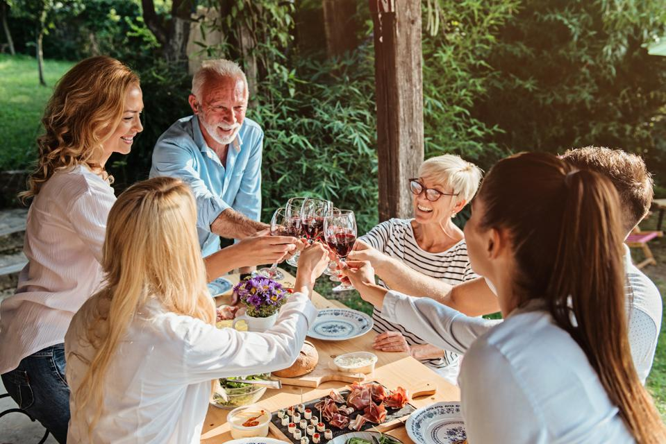 Family cheering over the dining table outdoors