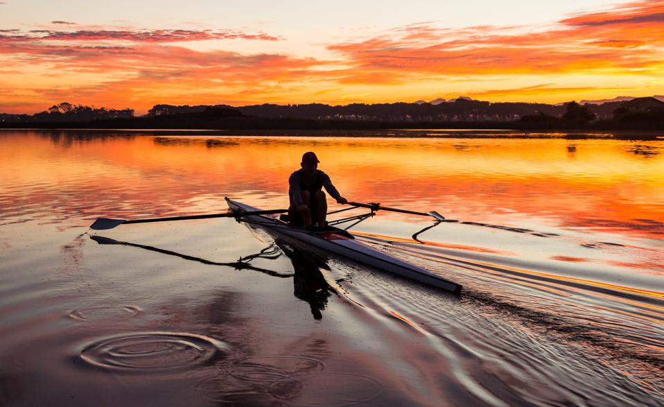 Mature man rowing a single scull on a lake at dawn