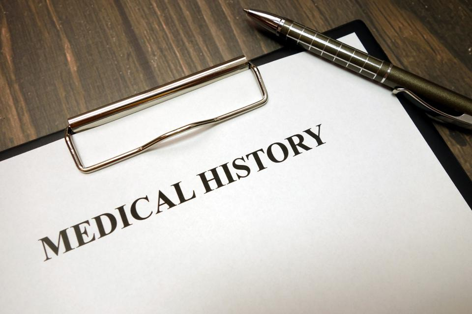 Clipboard with medical history and pen on desk