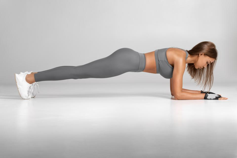 Fitness woman doing planking exercise, workout. Slim athletic girl training, isolated on the gray background