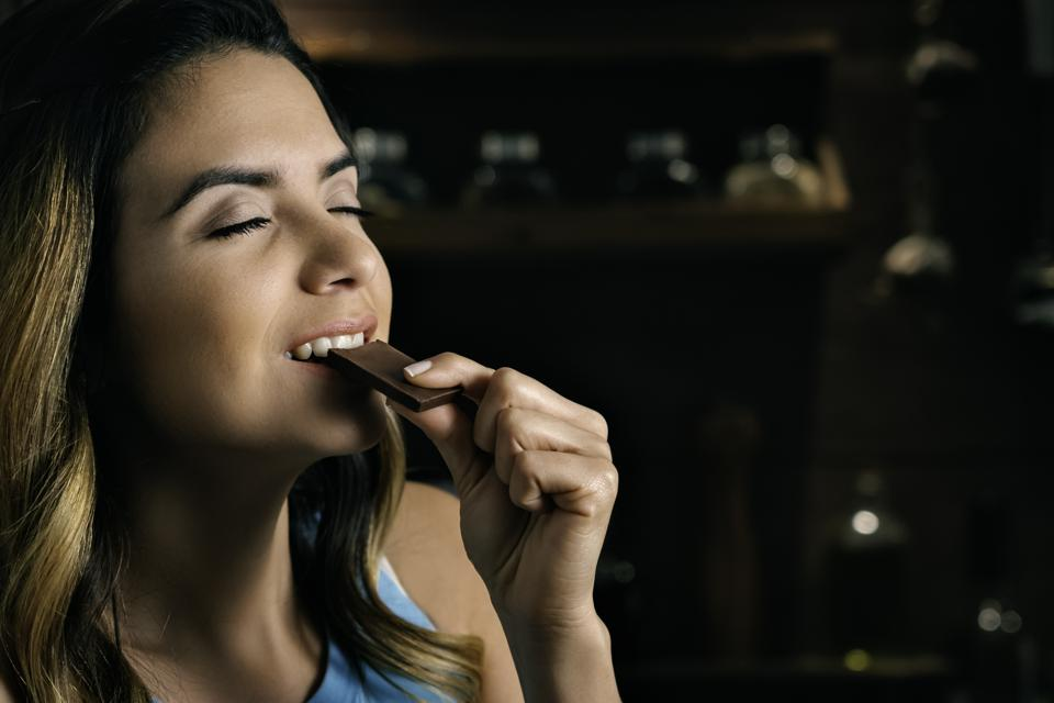 Close-up of a happy Hispanic woman eating indulgence chocolate in a rustic kitchen