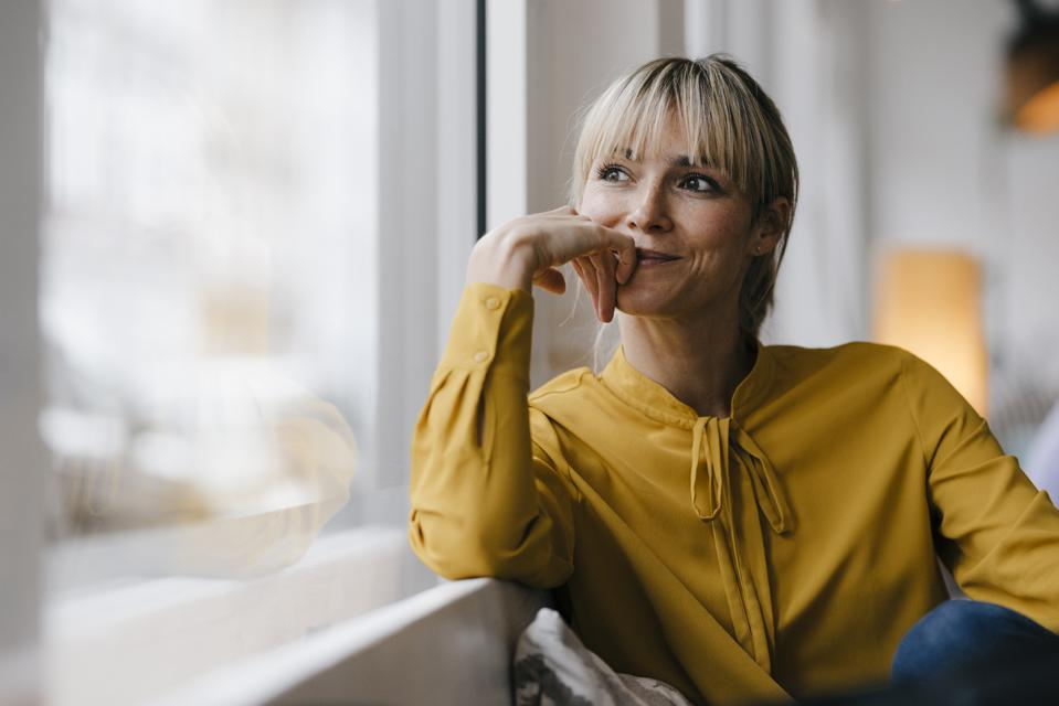 Portrait of a beautiful blond woman, looking out of window