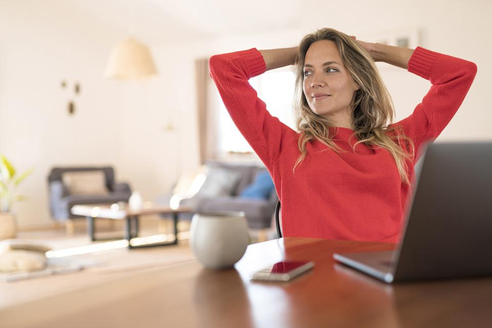 Woman sitting at dining table at home having a break from her work at the laptop