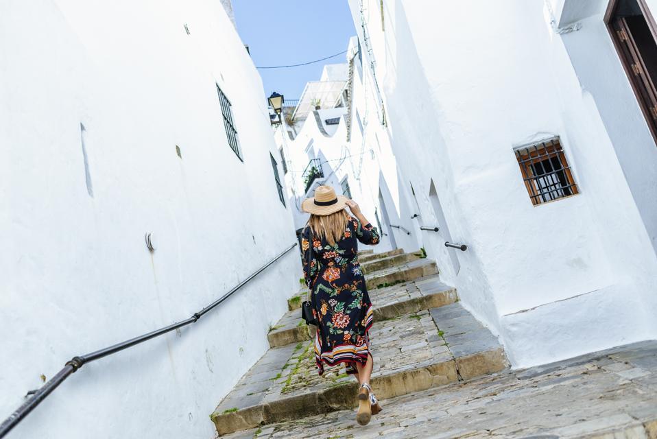Spain, Cadiz, Vejer de la Frontera, back view of fashionable woman walking through an alley