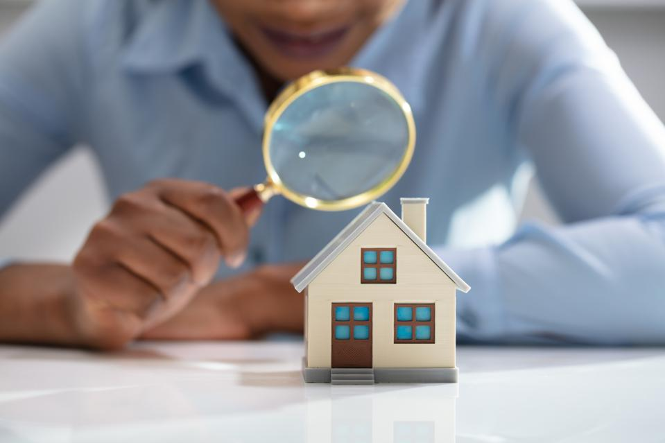 Businesswoman Holding Magnifying Glass Over House Model