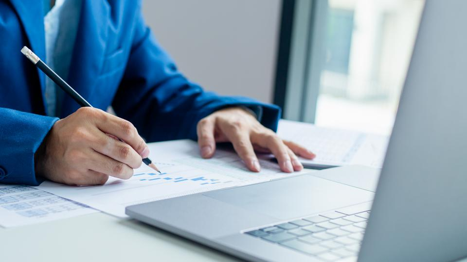 Businessman working and analysis on laptop with financial document data graph of business strategy and market growth at workplace.