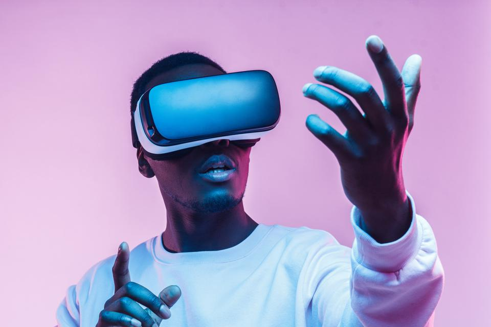 Young african american man playing game using VR glasses, enjoying 360 degree virtual reality headset for gaming, isolated on pink background