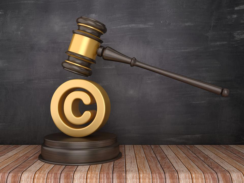 Gavel with Copyright Symbol on Chalkboard Background - 3D Rendering