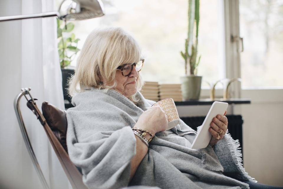 Retired senior woman wrapped in blanket holding coffee cup reading e-book in room at home