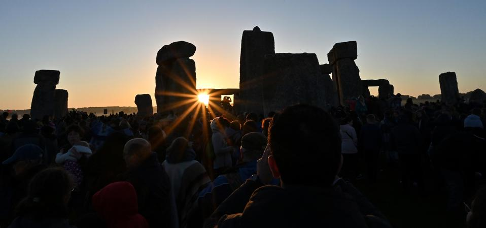 Revellers watch the sun rise at Stonehenge, near Amesbury, in Wiltshire, southern England on June 21, 2019, as they celerbate the Summer Solstice.  (Photo by Saeed KHAN / AFP) (Photo by SAEED KHAN/AFP via Getty Images)