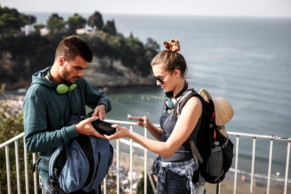 Hikers setting up music on bluetooth speaker and smart phone