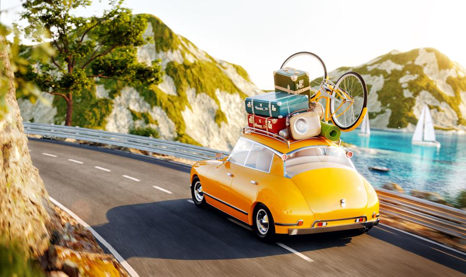 Cute little retro car with suitcases and bicycle on top goes by the road along beautiful harbor between mountain in summer day.