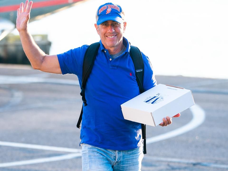 Jerry Seinfeld alone in New York City holding a box from a bakery and wearing a spring training baseball cap.