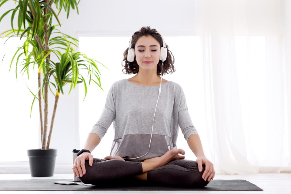 Modern woman with headphones sitting in yoga lotus posture