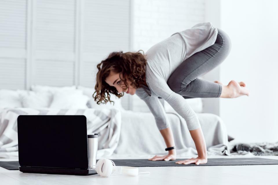 Adult woman doing bakasana yoga pose at home