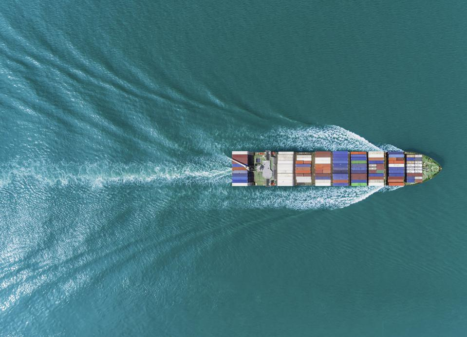 Aerial top view container ship on the green sea full load container for logistics, import export, shipping or transportation.