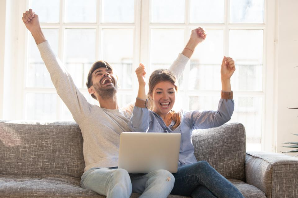 Happy young couple celebrate online victory, using laptop together