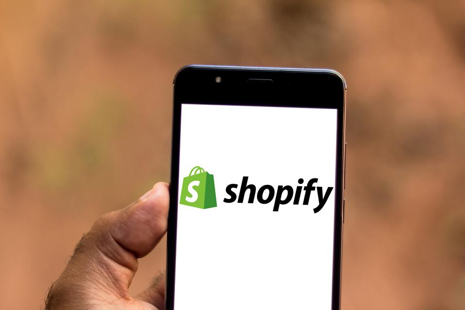 In this photo illustration a Shopify logo seen displayed on...