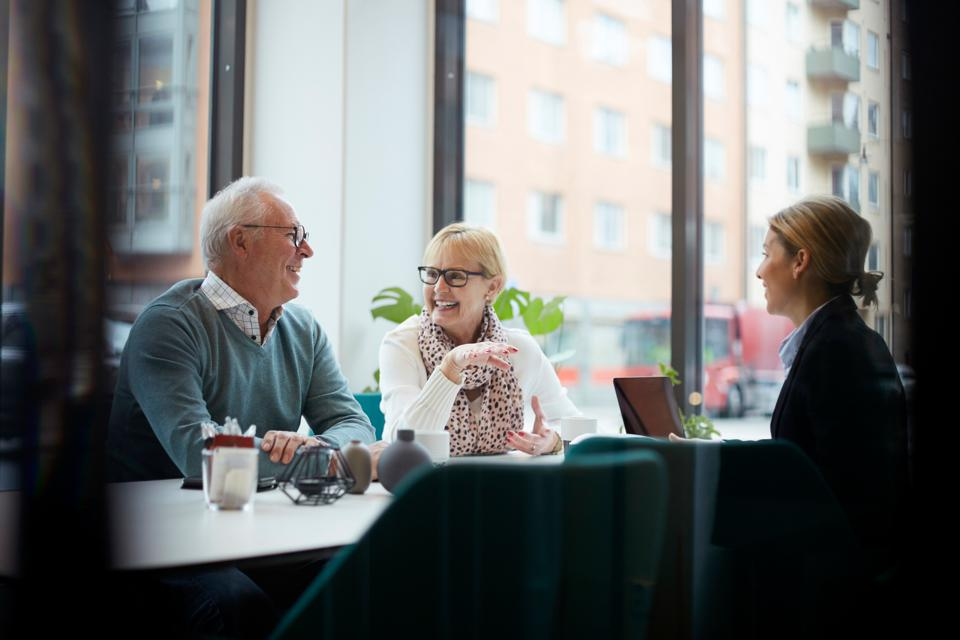 Smiling senior couple talking while sitting with realtor in office