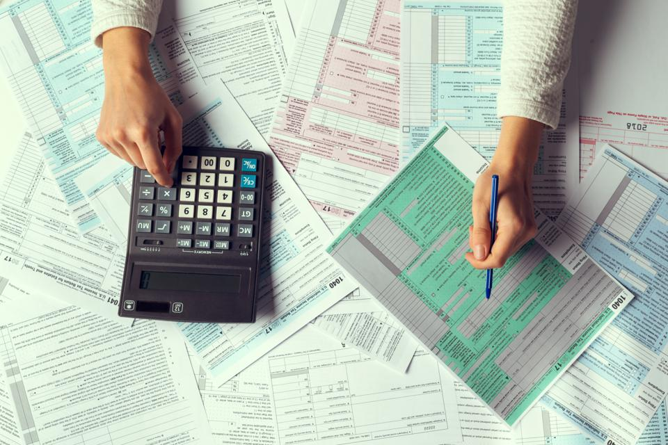 A person with a calculator and tax forms.