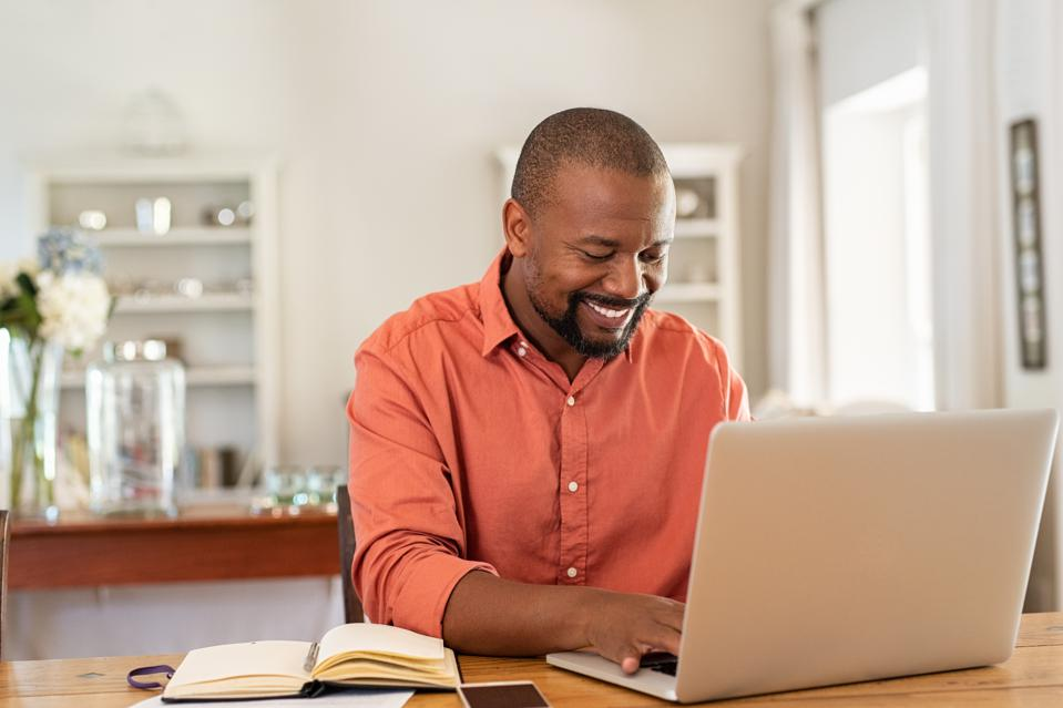 Happy mature black man using laptop