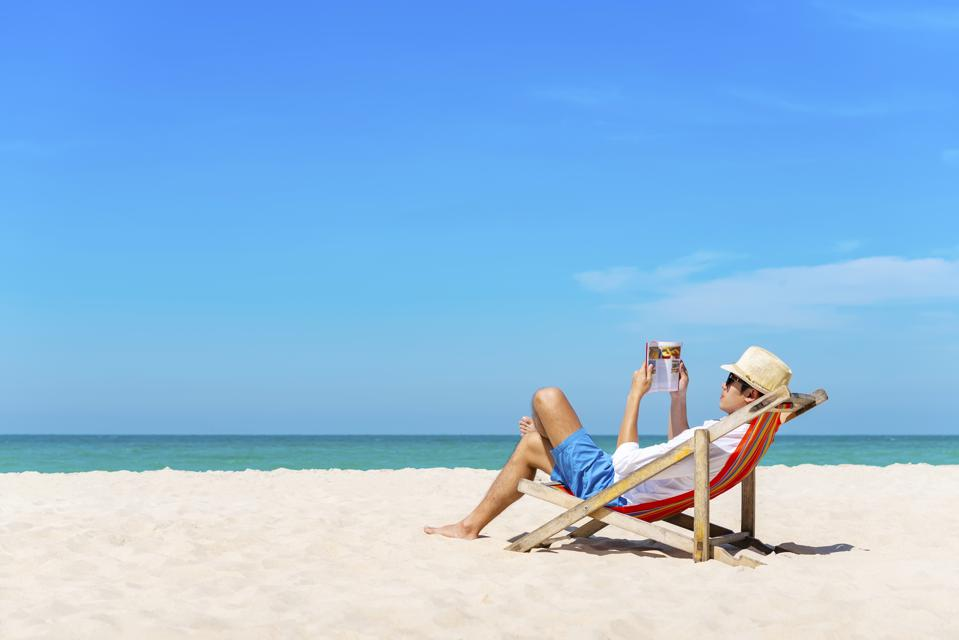 Young man reading on the tropical beach with blue sky on vacation. Travel and summer time.