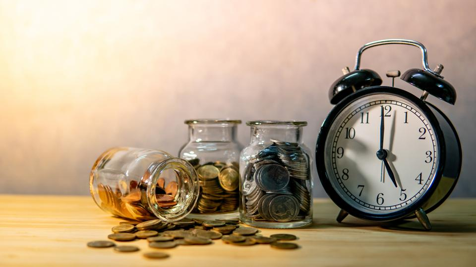 Coin jars and clock. Saving money for retirement