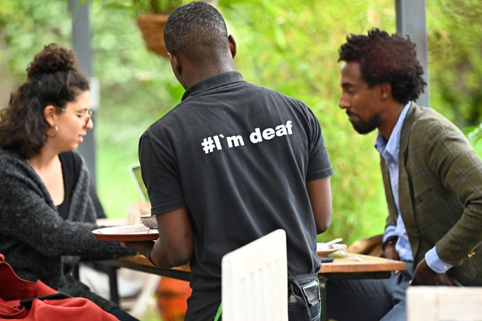 A restaurant in Kenya where a deaf waiter is serving to customers at a cafe. He is wearing a shirt that says # I'm deaf.