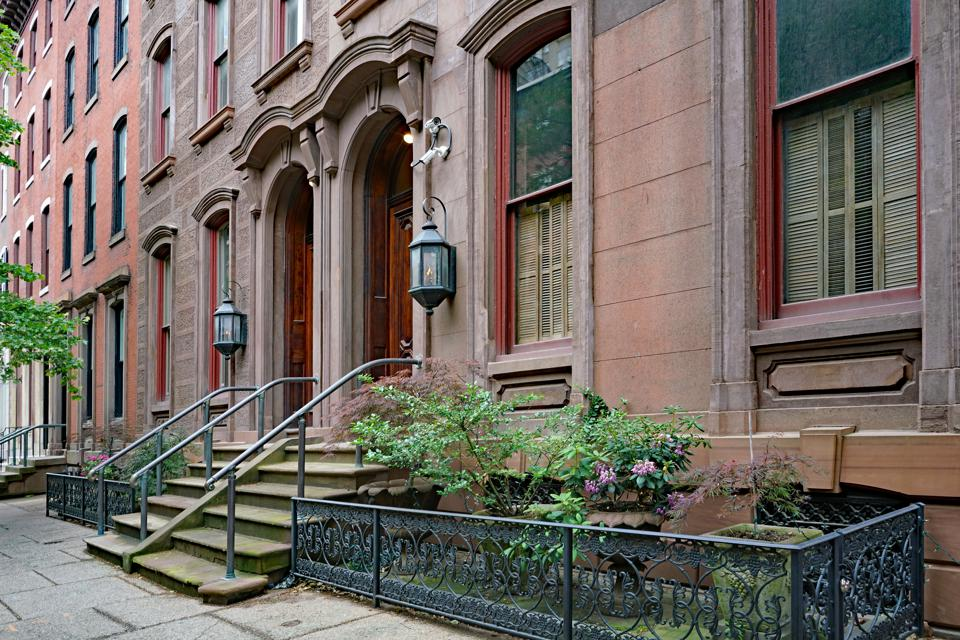 urban street with elegant old brownstone style townhouses or apartment buildings