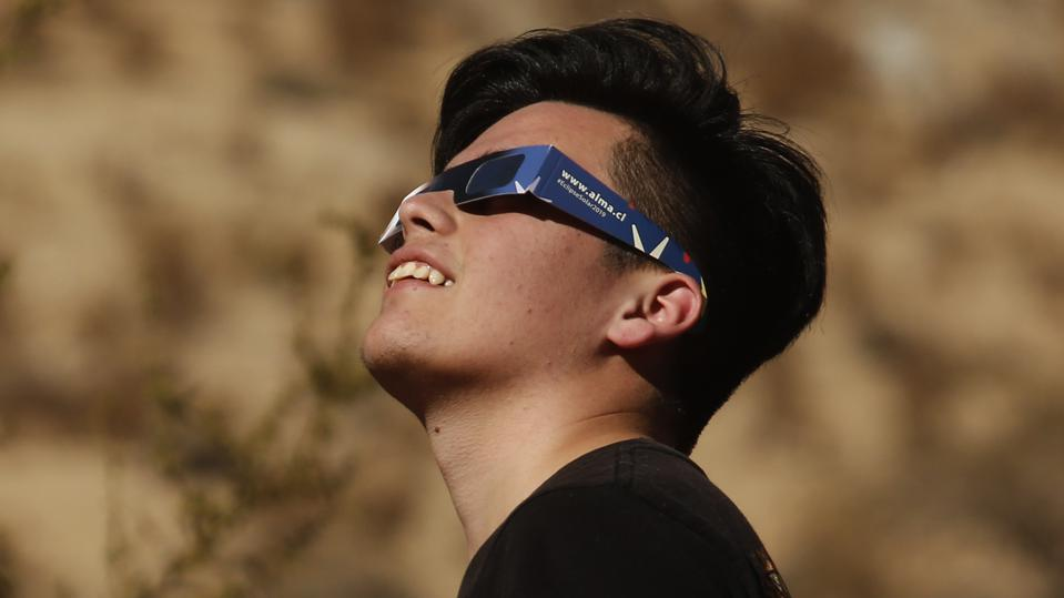 A young Chilean watches the sky with eclipse glasses prior to a total solar eclipse on July 2, 2019 in Paiguano, Chile. (Photo by Marcelo Hernandez/Getty Images)