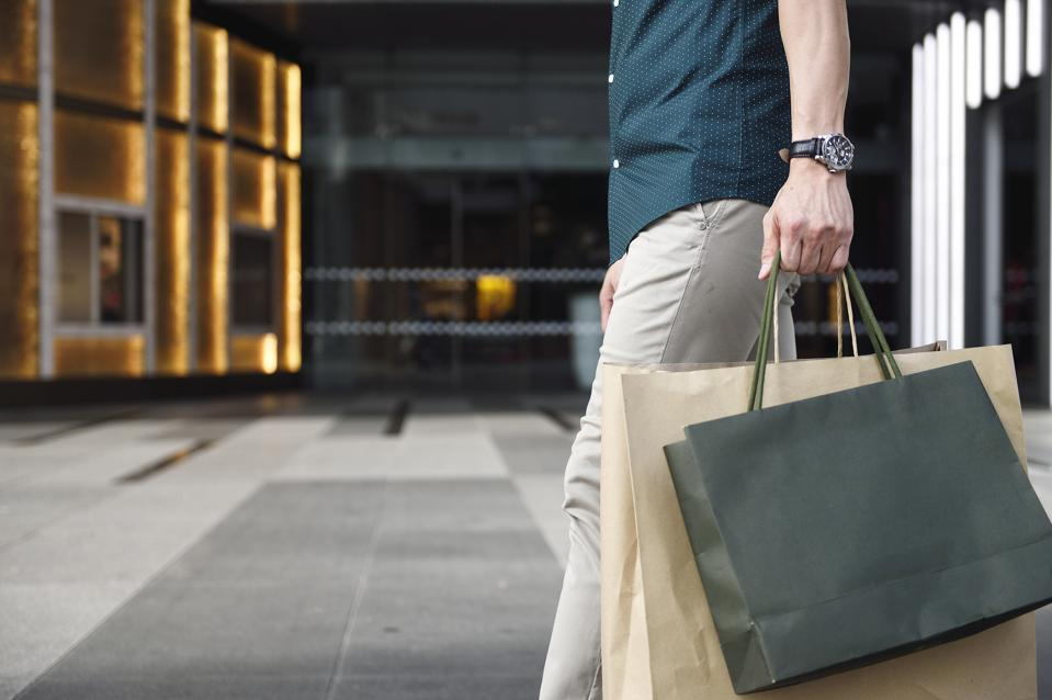 Man's legs and shopping bags outside a luxury mall
