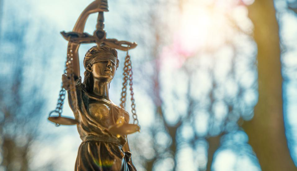 Close-Up Of Lady Justice Statue Against Bare Trees