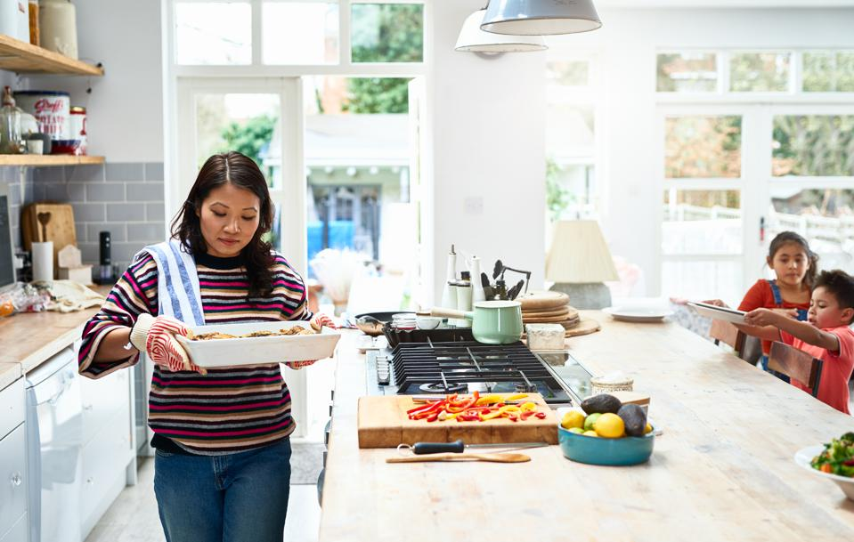 Woman holding hot casserole dish in kitchen