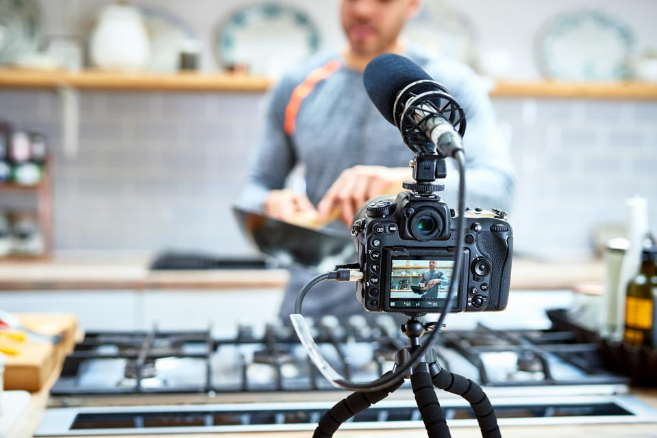 Video camera set up to film man cooking in kitchen