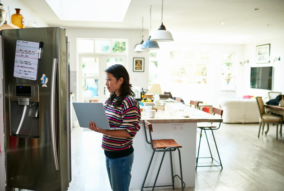 Woman using laptop by fridge and buying food online