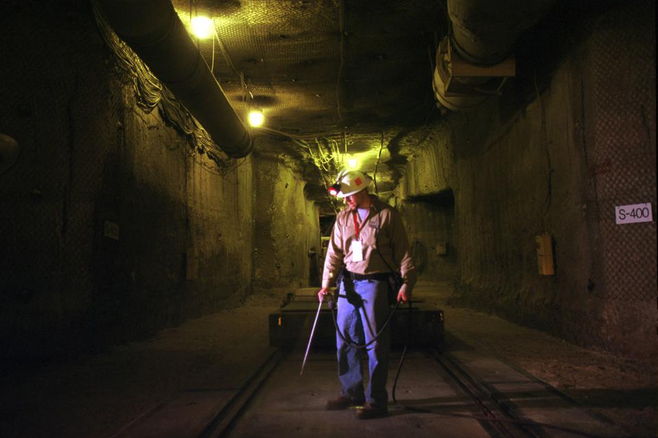 Man in tunnel using air compressor