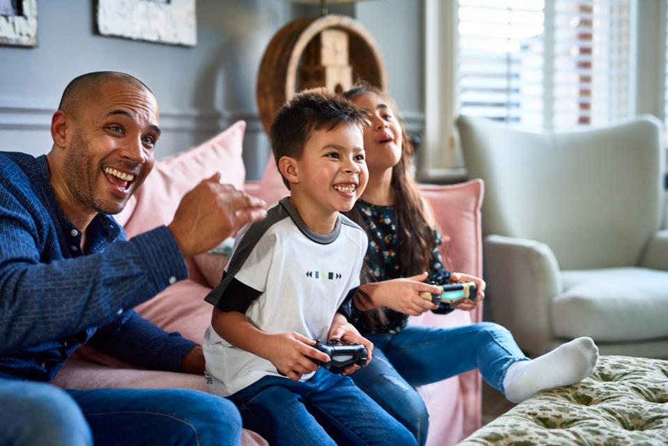 Excited father watching son and daughter play video game