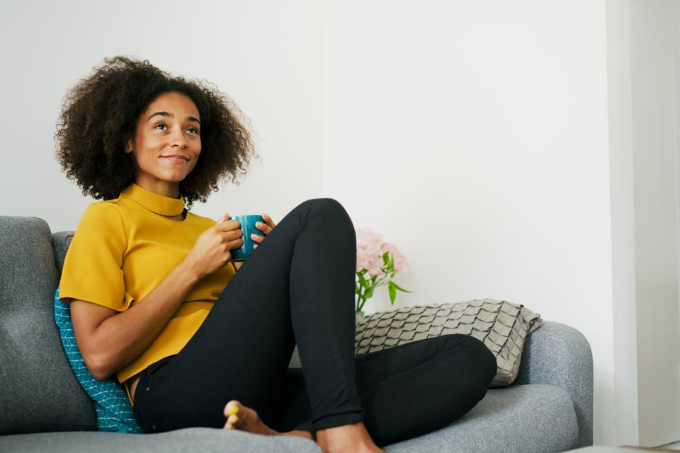 Woman relaxing on sofa with hot drink