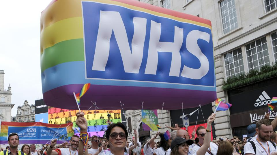 NHS Staff march with a huge NHS rainbow inflatable during...