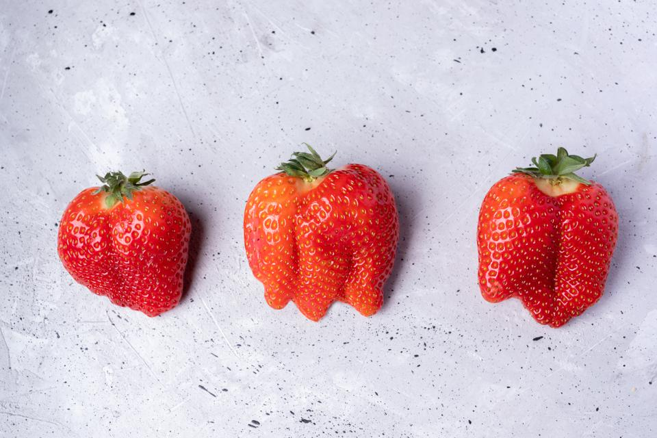 Three imperfect ripe strawberries.