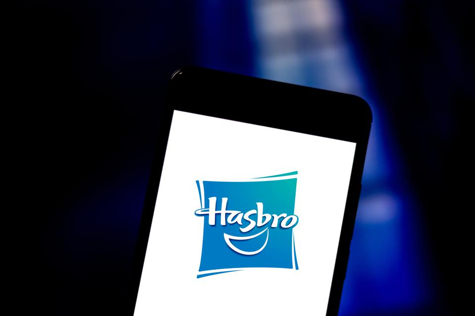 In this photo illustration a Hasbro logo seen displayed on a...