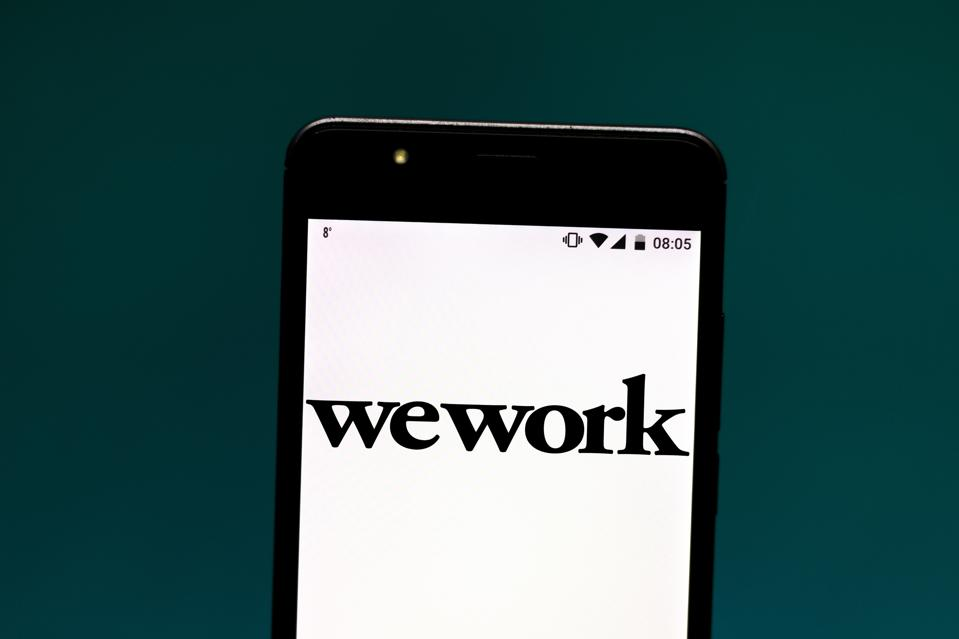 In this photo illustration a WeWork logo seen displayed on a...