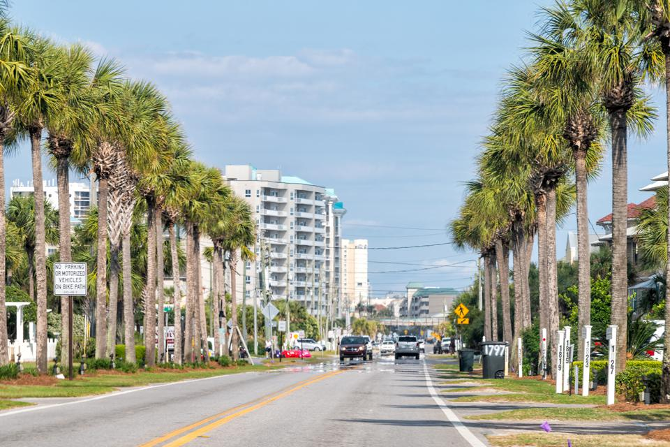 Street road in Miramar beach city town with condominium condo apartment buildings, palm trees and cars in summer, Florida panhandle