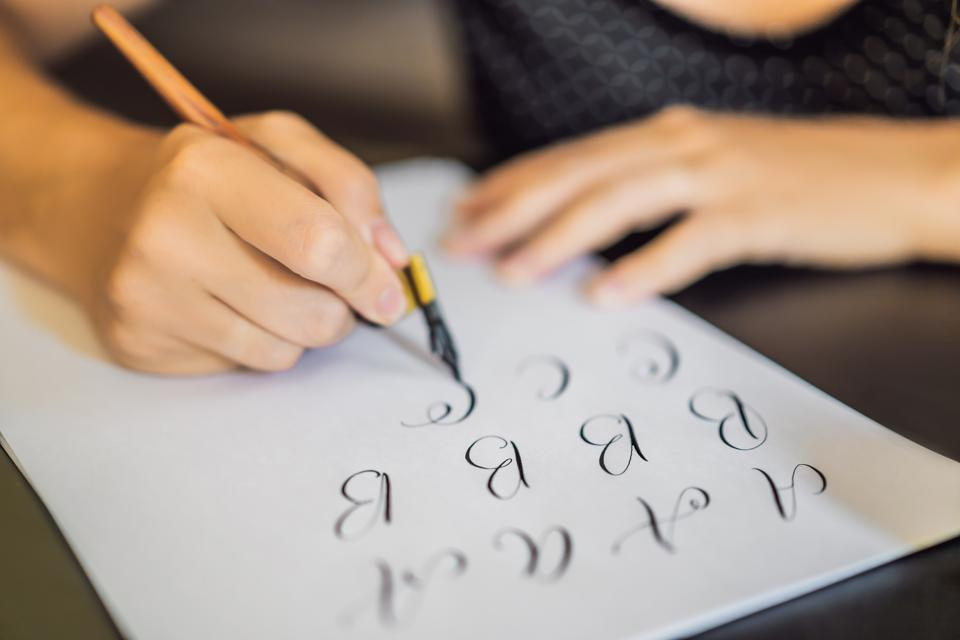 A woman practices hand lettering on white paper