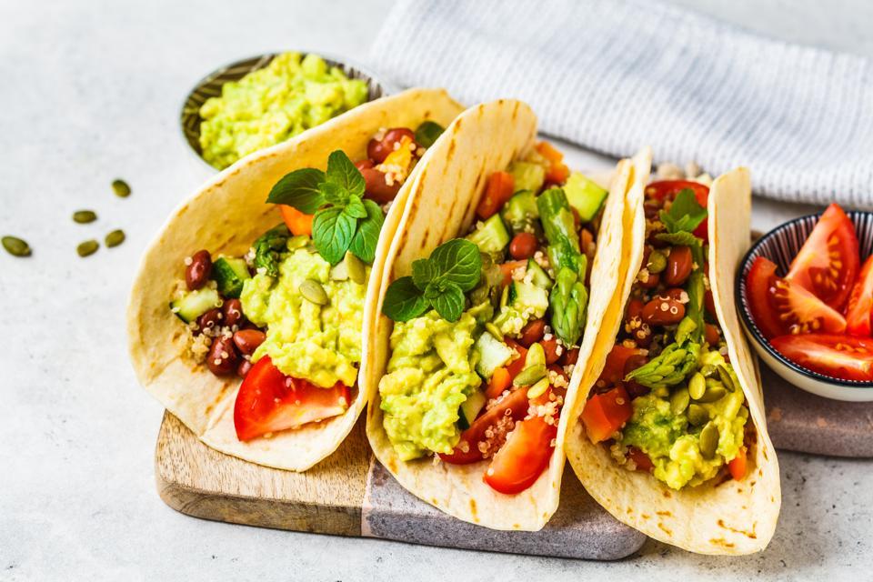 Vegan tortilla wraps with quinoa, asparagus, beans, vegetables and guacamole.