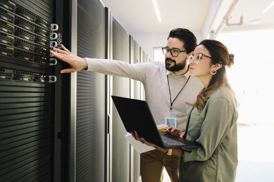 IT technicians examining equipment in network server room