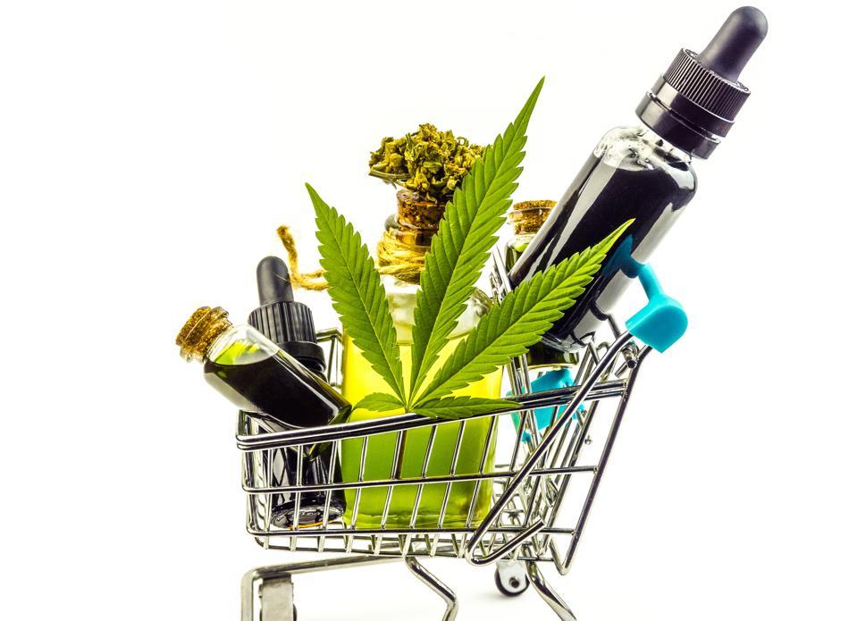 Purchasing Cannabis oil concept, Cannabis CBD oil bottles in miniature shopping cart